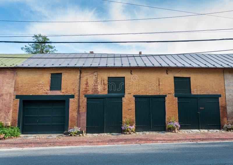 Gammalt tegelstenlager med metalltak- och ladugårddörrar i centrum, royaltyfri bild