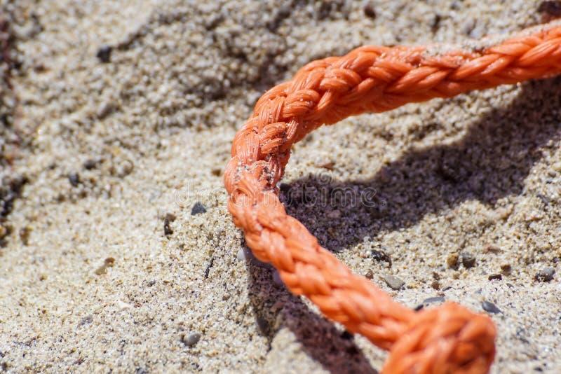 Gammalt tjockt nautiskt rep på sandjordningen fotografering för bildbyråer