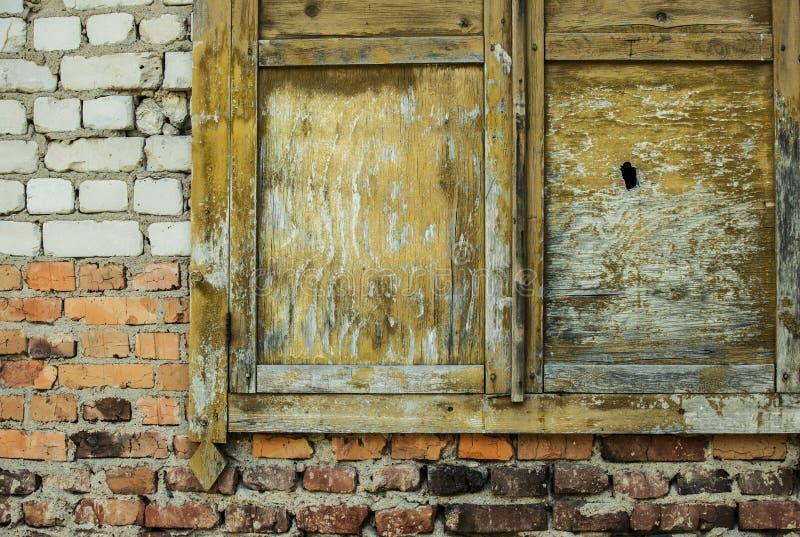 Gammalt träfönster på brun bakgrund för tegelstenvägg arkivfoto