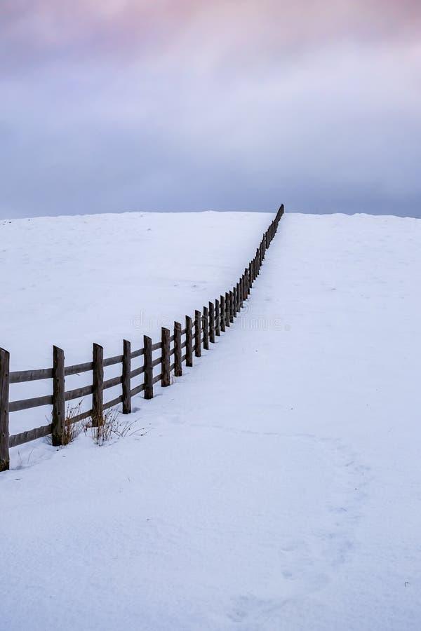 Gammalt träfarmestaket i ett lantligt landskap för vinter med mörk moln och snö royaltyfri bild