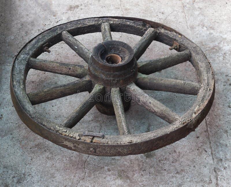 Gammalt trähjul från en hästdragen vagn på en konkret bakgrund, närbild, trähjul arkivfoto