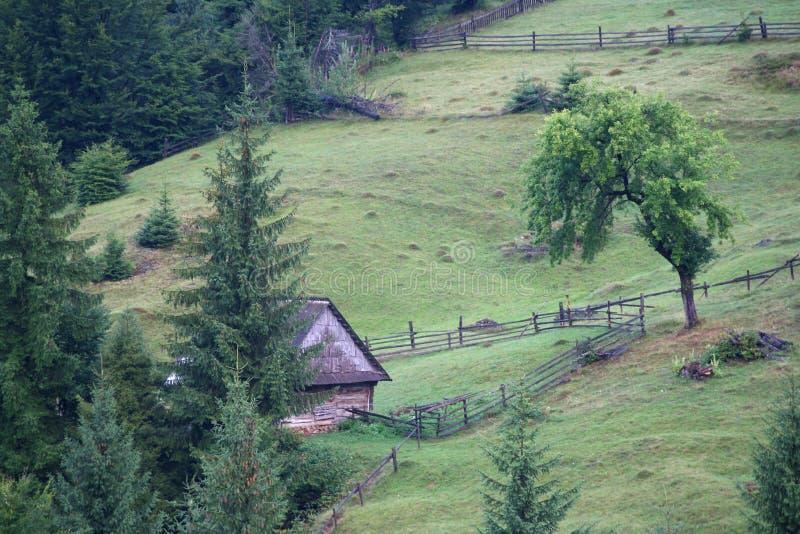 Gammalt trähus i bergen som omges av ett staket royaltyfri foto