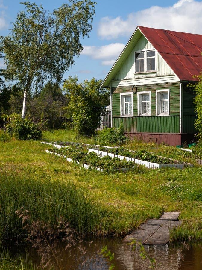 Gammalt trähus i lantlig grönsakträdgård royaltyfria foton