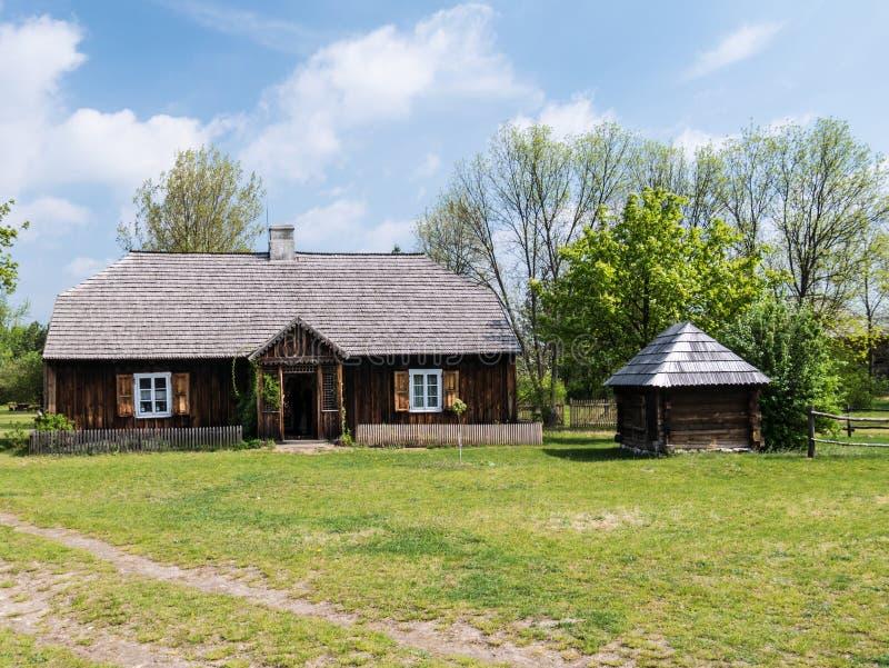 Gammalt trähus med en brunn royaltyfri foto