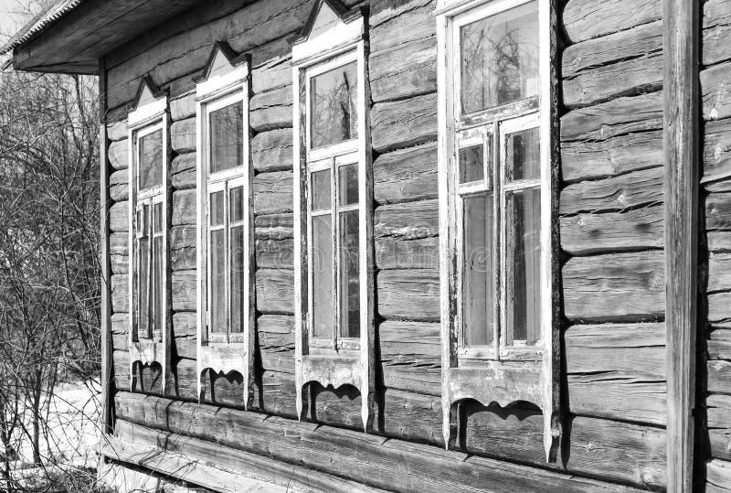 Gammalt trähus med fönster i den svartvita trädgården royaltyfria bilder
