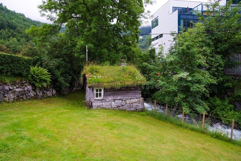 Gammalt trähus med grästaket i Geiranger, Norge Traditionellt norskt byhus på sommarlandskap Arkitektur som är trad royaltyfri bild