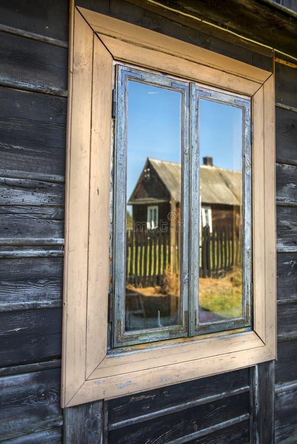 Gammalt trähusfönster med reflexion i exponeringsglaset royaltyfri fotografi