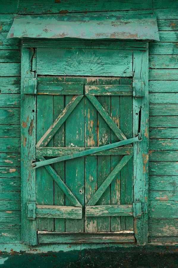 Gammalt trälandsfönster med stängda slutare målad gräsplan arkivbild