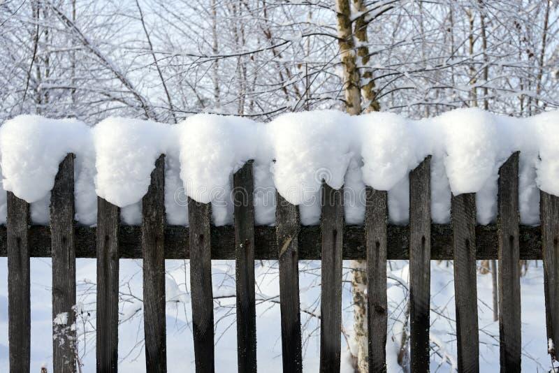 Gammalt trälandsstaket som täckas med ett tjockt lager av en vit fluffig insnöad vinter arkivfoto