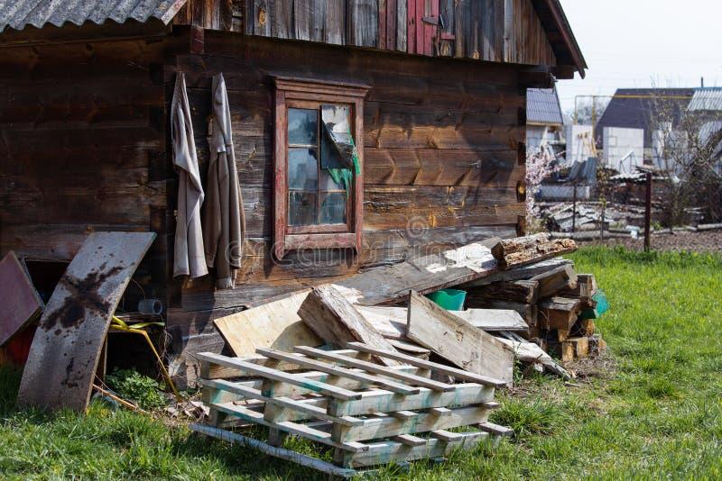 Gammalt trälantligt hus med konstruktionsavfalls i gården royaltyfri foto