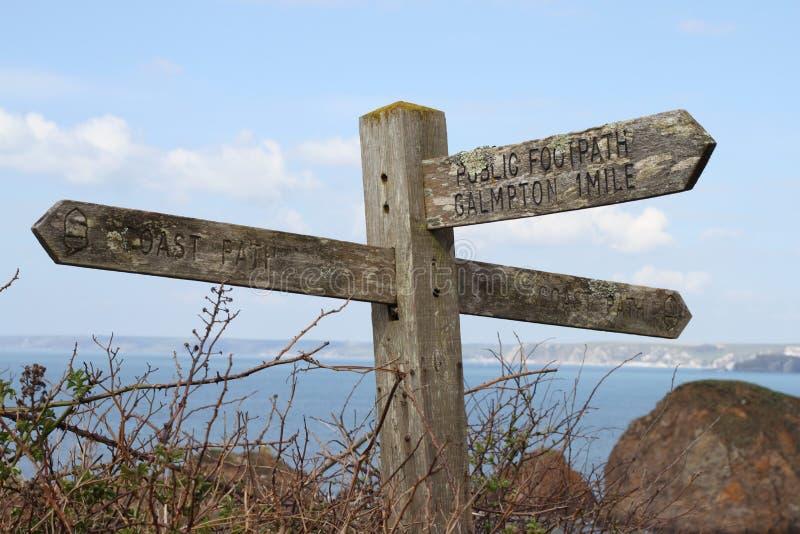 Gammalt träoffentligt vandringsledtecken som förbiser hopplilla viken i Devon, Förenade kungariket arkivbild