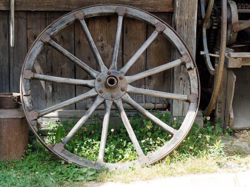 Gammalt trävagnhjul som lutar mot en trävägg fotografering för bildbyråer