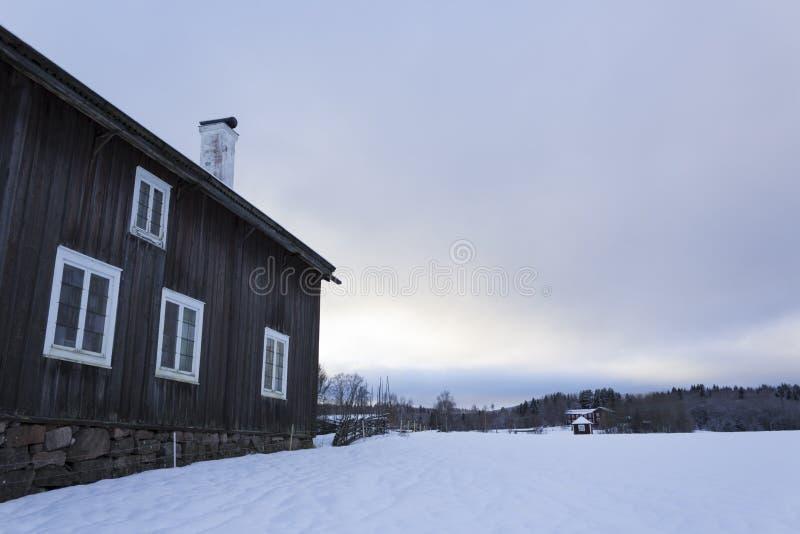 Gammalt - traditionellt - hus i lantliga Sverige och ett vintrigt landskap på en härlig vinterdag royaltyfri foto