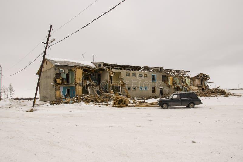 Gammalt två-storied förstört, fördärvat och ödelagt hus i vinter med snö omkring Armod och misär som är norr arkivbild
