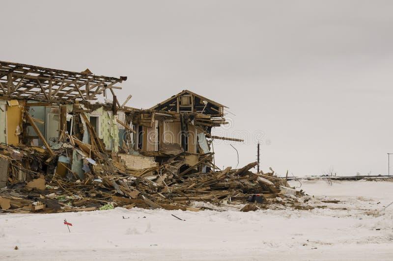 Gammalt två-storied förstört, fördärvat och ödelagt hus i vinter med snö omkring Armod och misär som är norr arkivfoto