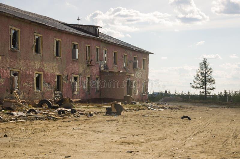 Gammalt två-storied förstört rött hus i höst med sand omkring Armod och misär som är norr arkivfoto