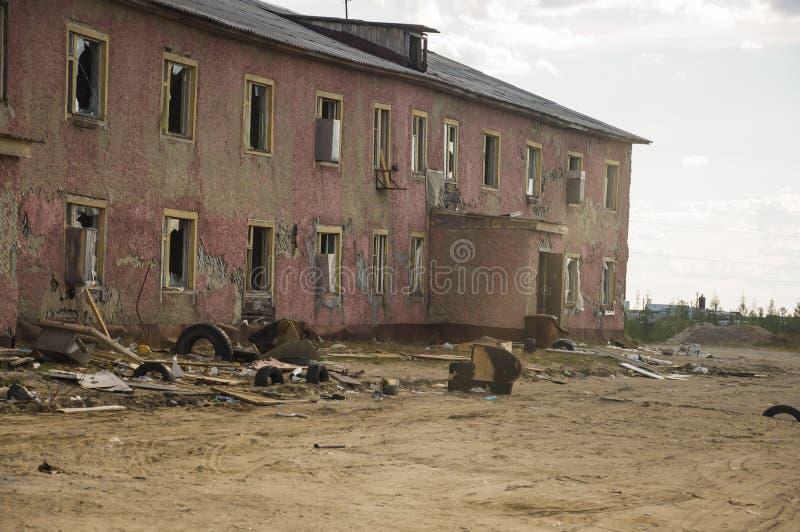 Gammalt två-storied förstört rött hus i höst med sand omkring Armod och misär som är norr arkivbilder