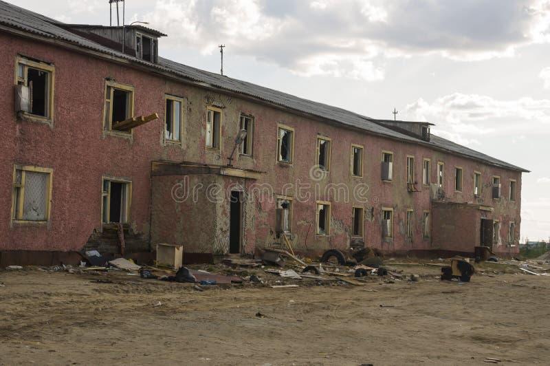 Gammalt två-storied förstört rött hus i höst med sand omkring Armod och misär som är norr royaltyfri fotografi