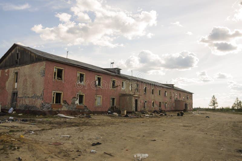Gammalt två-storied förstört rött hus i höst med sand omkring Armod och misär som är norr royaltyfri bild