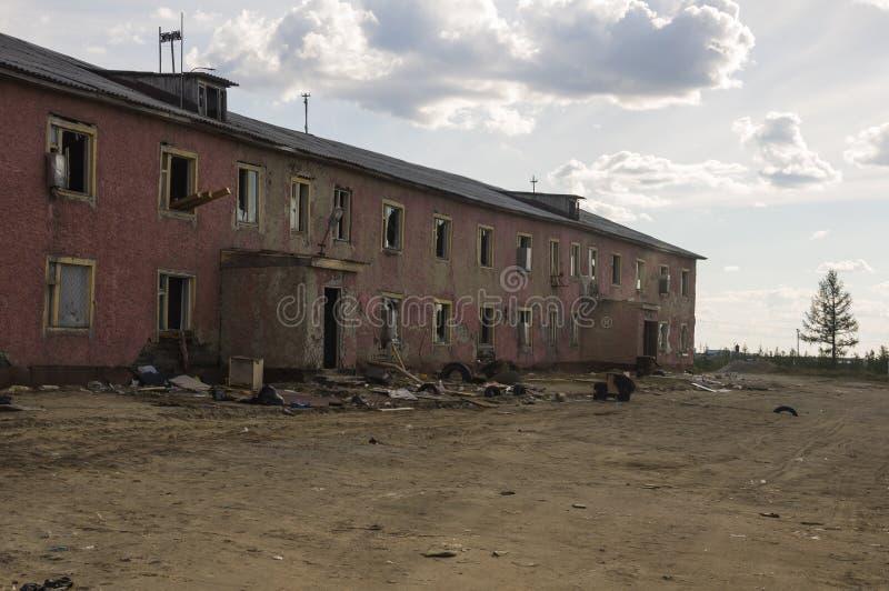 Gammalt två-storied förstört rött hus i höst med sand omkring Armod och misär som är norr royaltyfria foton