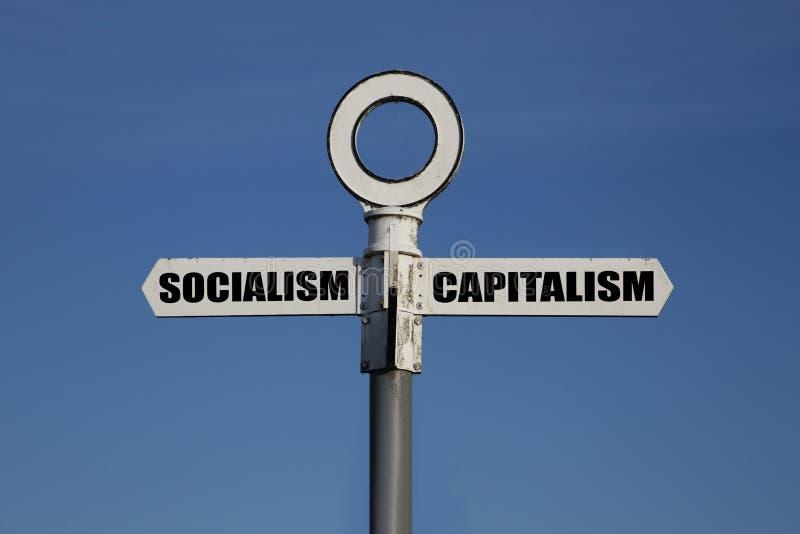 Gammalt vägmärke med socialism och kapitalism som pekar i motsatta riktningar royaltyfria foton