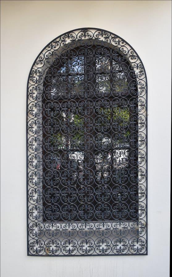 Gammalt Venetian fönster med svart järnraster arkivfoto