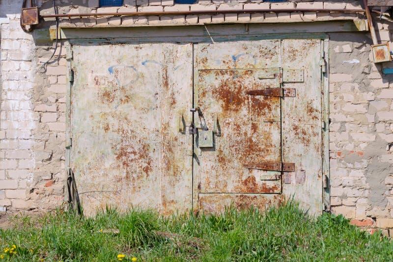 Gammalt vitt tegelstengarage med den rostiga porten arkivfoton