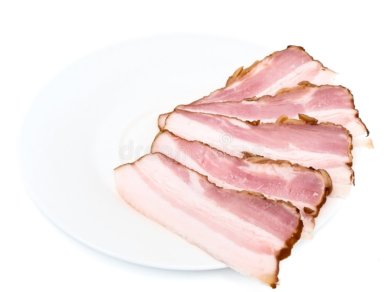 Gammon of bacon. On the white saucer royalty free stock photos