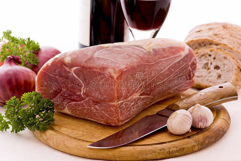 Gammon with Bread and Wine. Gammon Piece on a wooden plate with bread and wine royalty free stock photography