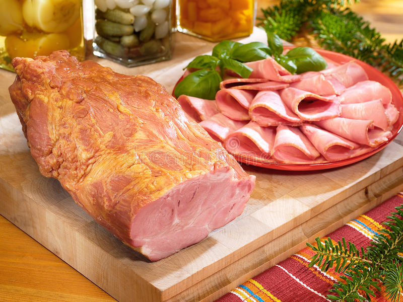 Gammon on a cutting board with preserves. Gammon on a cutting board with canned food royalty free stock images