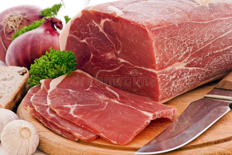 Gammon with Herbs. Gammon slices with herbs and a knife as closeup on a wooden plate stock image