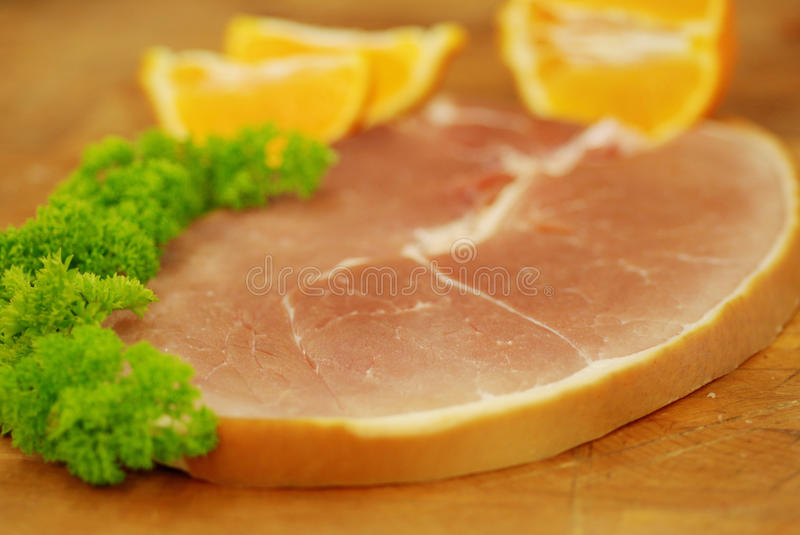 Gammon Slice. With parsley and oranges on butcher's block stock photography