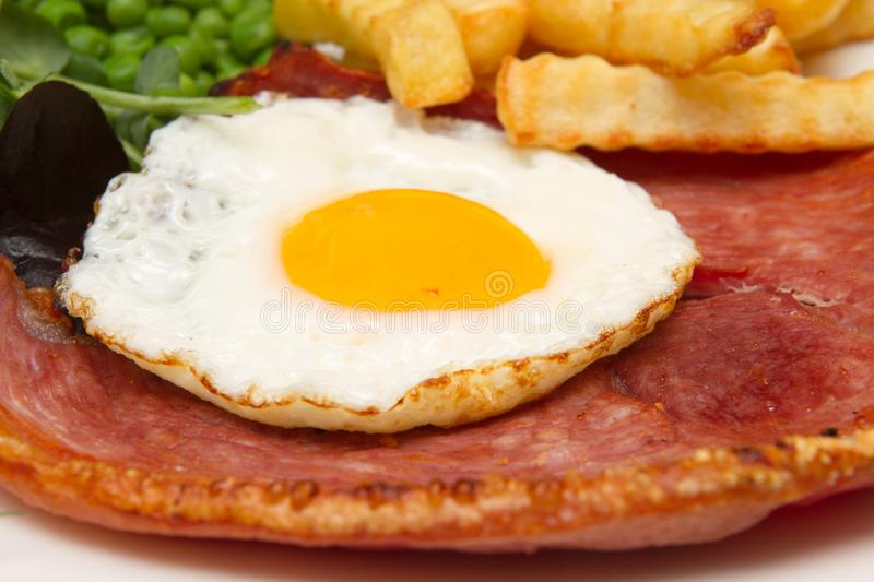 Gammon steak with a fried egg. A traditional pub lunch of gammon steak with a fried egg stock image
