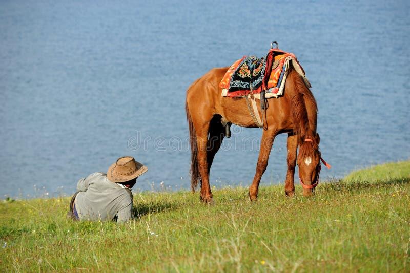 Ganaderos chinos del Kazakh con el caballo en el lago Sailimu fotos de archivo