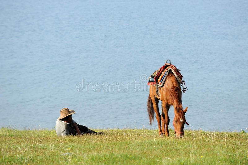 Ganaderos chinos del Kazakh con el caballo en el lago Sailimu imagenes de archivo