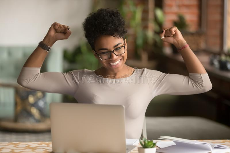 Ganador africano emocionado de la sensación de la mujer que disfruta triunfo en línea en el ordenador portátil fotografía de archivo