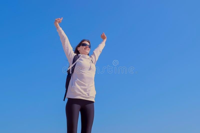 Ganador feliz de la mujer en actitud de la victoria con el aumento de las manos en fondo del cielo azul imagenes de archivo