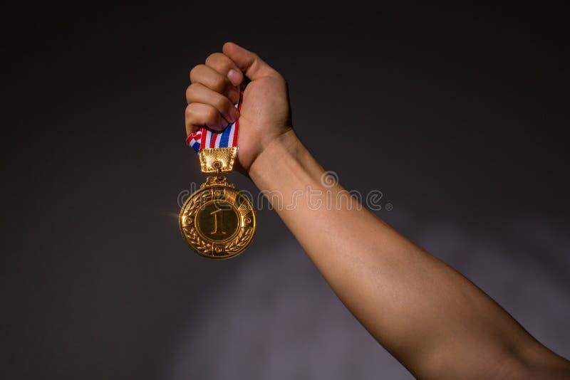 Ganador que sostiene la moneda de oro del número uno fotografía de archivo