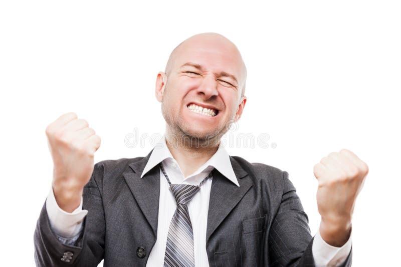 Ganador sonriente del hombre de negocios que gesticula el puño aumentado de las manos que celebra el logro de la victoria foto de archivo