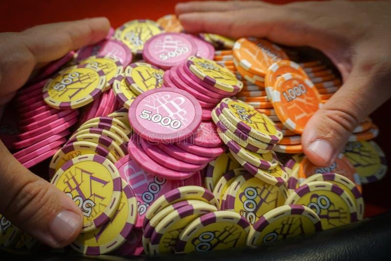 Gancho agarrador del ganador muchas fichas de póker Éxito y suerte en el juego fotos de archivo