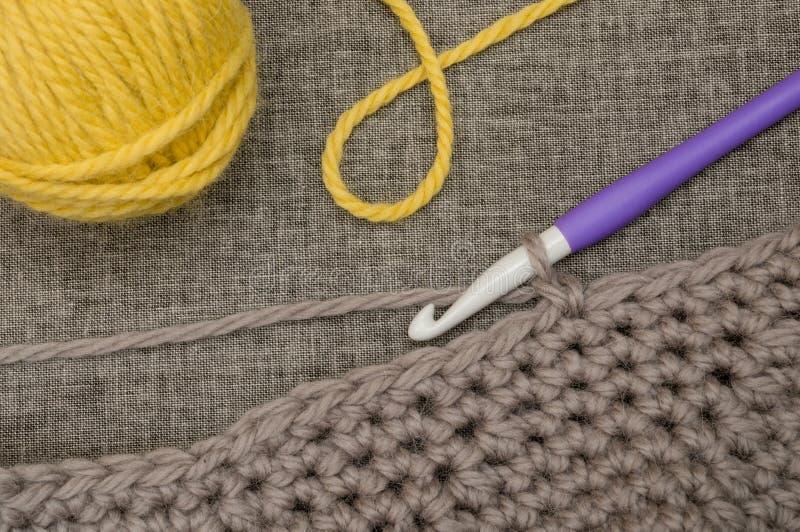 Gancho de confecção de malhas, Gray Wool feito crochê, e bola do fio amarelo imagens de stock royalty free