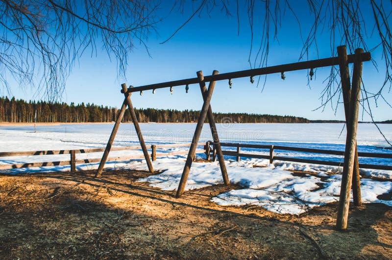 Gancho de madeira na frente de um lago congelado com os pinheiros do vidoeiro em torno quando ramos que penduram do céu azul imagens de stock