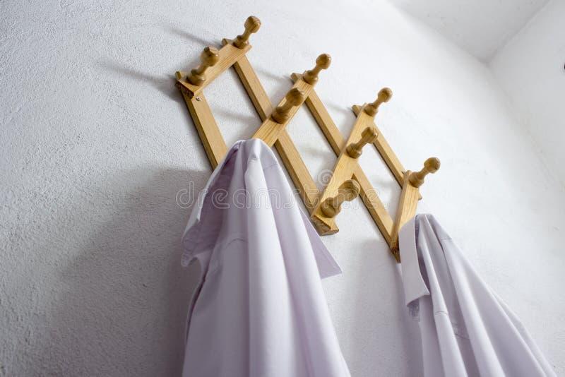 Gancho de pano de madeira da parede com as duas camisas brancas imagens de stock