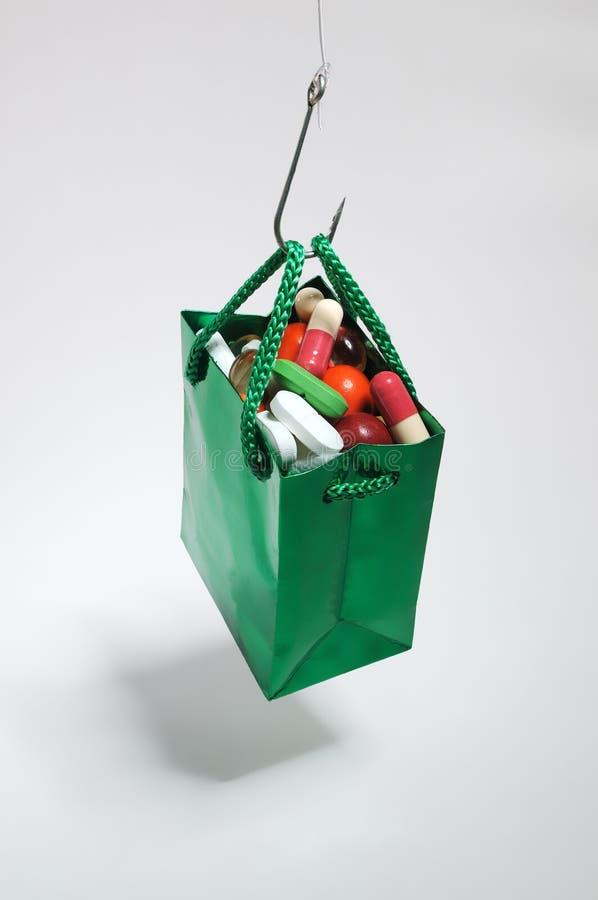 Gancho de pesca que guarda um saco verde com medicinas imagem de stock royalty free