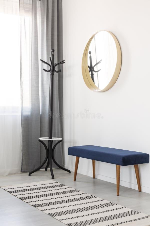 Gancho de revestimento, canapé azul e espelho redondo no quadro de madeira no salão espaçoso imagem de stock