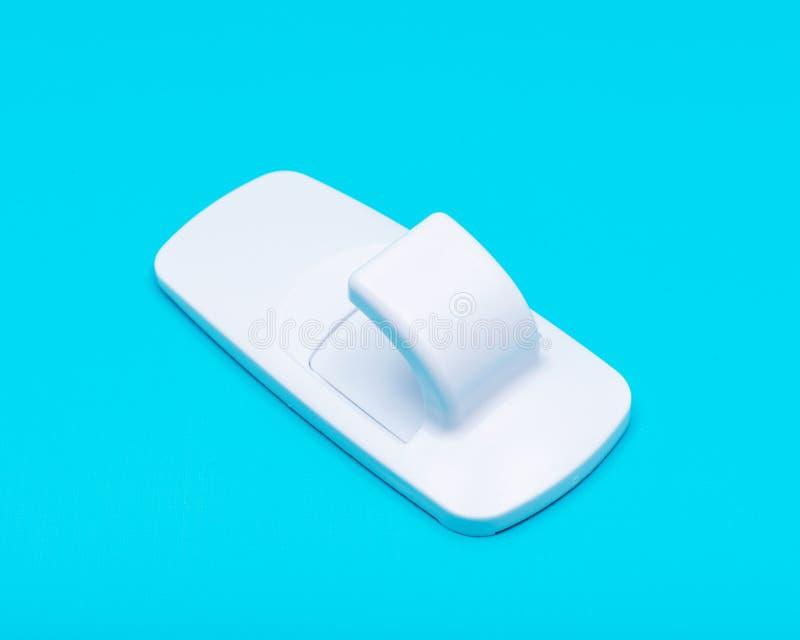 Gancho de serviço público da parede do jumbo plástico branco com a suspensão Dano-livre isolada no azul foto de stock royalty free