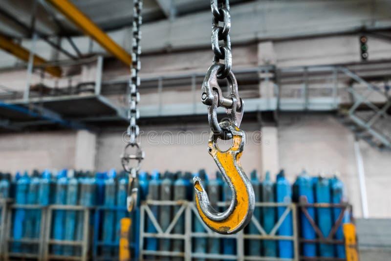 Gancho industrial metálico para levantar cosa pesada en la fábrica Ganchos de la grúa en una cadena gruesa dentro del piso de la  imágenes de archivo libres de regalías