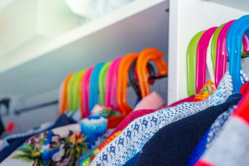 Ganchos coloridos da criança com as camisas do menino da criança que penduram em um armário imagens de stock