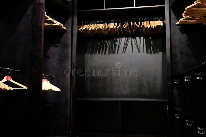 Ganchos de roupa de madeira vazios que penduram no armário e em sombras profundas de moldação fotografia de stock