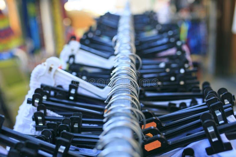 Ganchos plásticos pretos com roupa imagem de stock